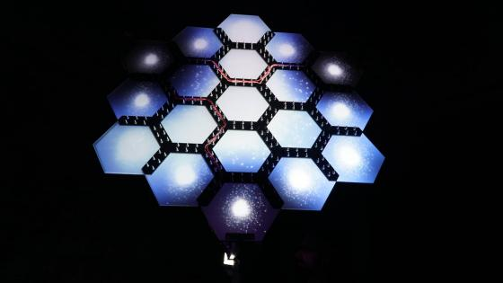 Tycho is an interactive object that mimics the shape and behaviour of the James Webb Space Telescope by capturing light with a sensor and transmitting its colour via LEDs to a mirrored hexagonal surface, where it modulates a projection sequence inspired by images of the birth and death of stars.